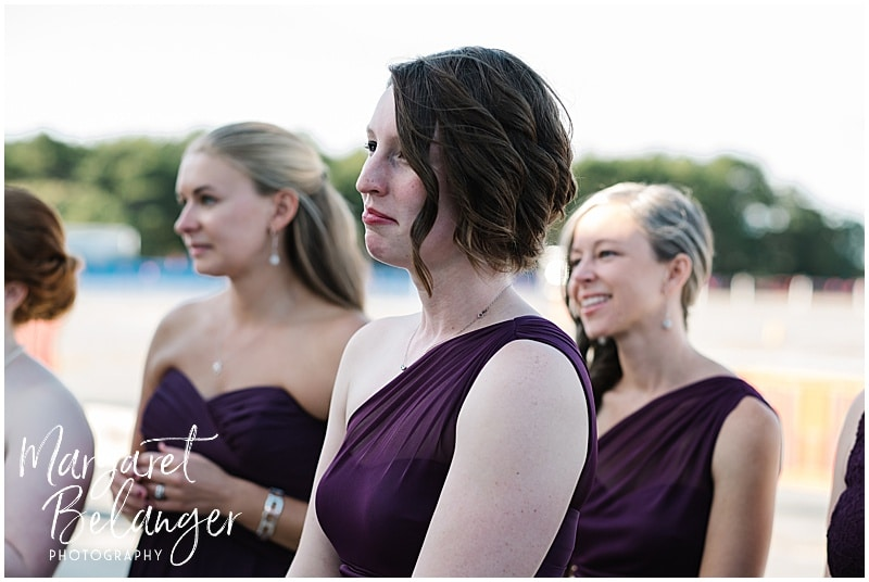 Bridesmaids at Horseneck Beach look on as bride and groom see each other for first time