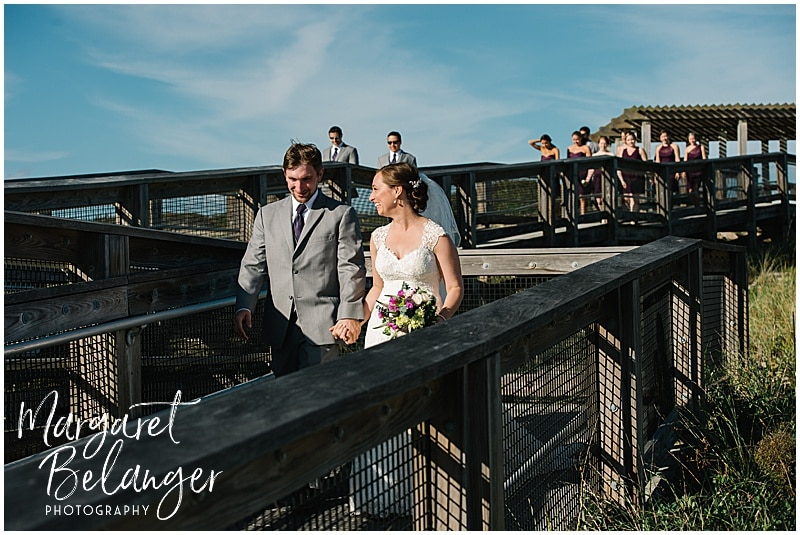 Bride and groom walk down boardwalk, followed by their wedding party, at Horseneck Beach