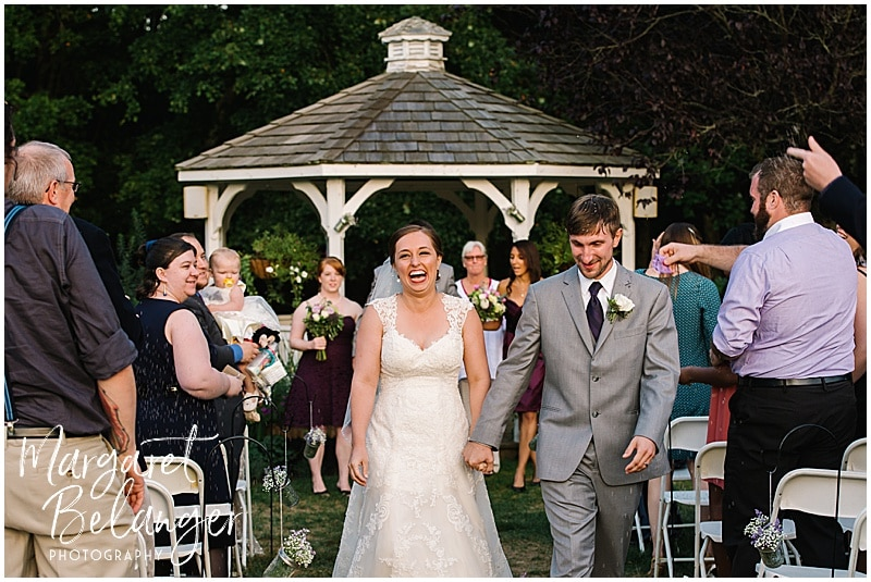 Newly married couple joyfully walk back down the aisle at a Bittersweet Farm wedding