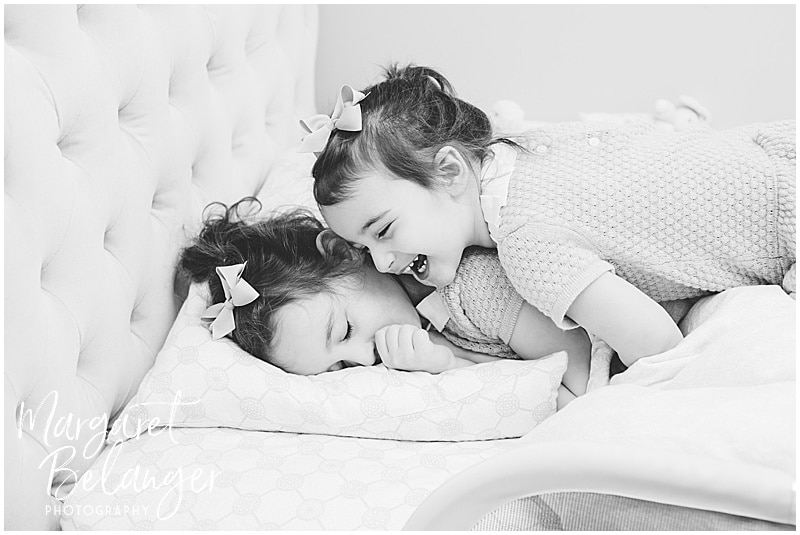 Brookline newborn session, sisters playing on bed