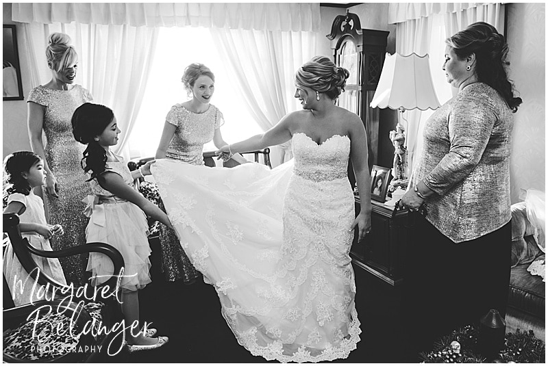 black and white photo of bridesmaids fixing bride's train