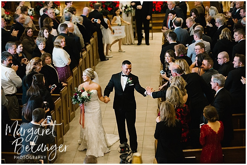Bride and groom process down aisle at the end of their winter wedding ceremony