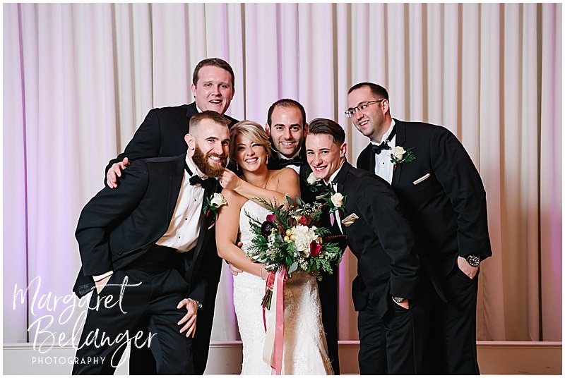 Casual photo of the bride posing with the groomsmen