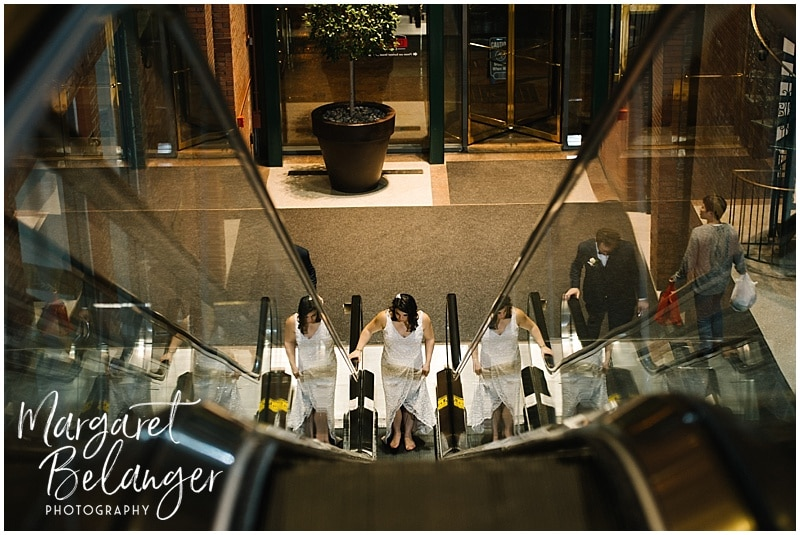 Bride coming up the escalator with her reflection on either side