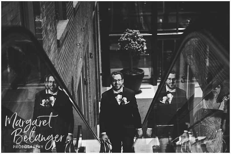 black and white photo of the groom coming up the escalator with his reflections on either side