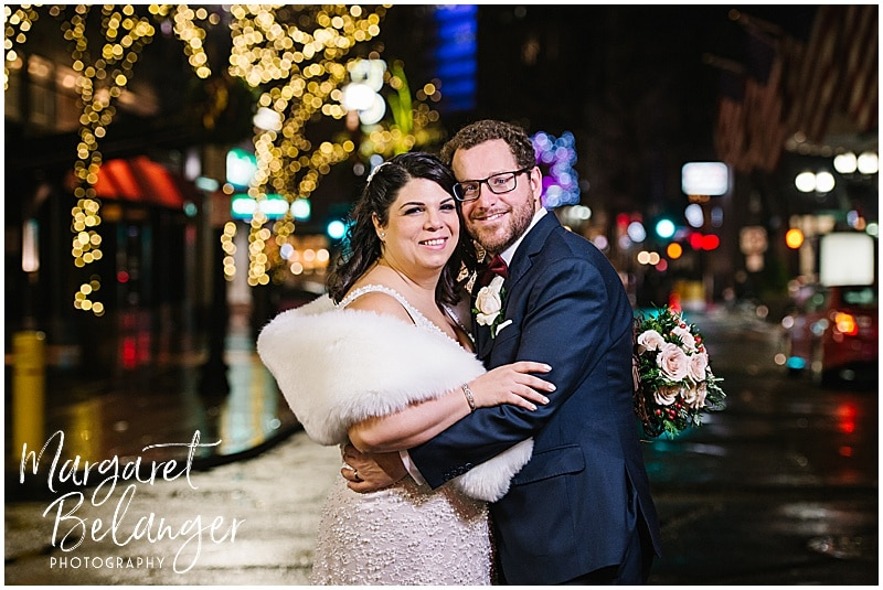 Outdoor winter wedding portraits of the bride and groom. The bride carries her bouquet and is wearing a white fur stole as they pose in front of city Christmas lights.