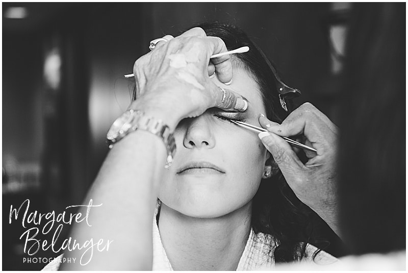 Black and white photo of bride having her eye make=up done