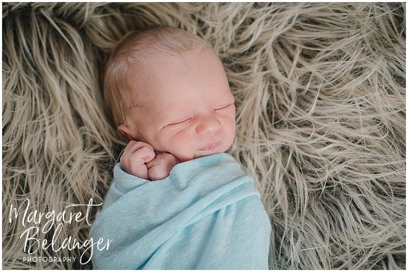 Lowell newborn session, baby in blue swaddle on furry blanket