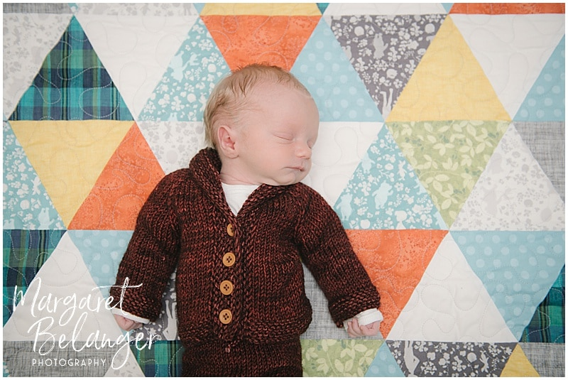 Lowell newborn session, baby in hand knit suit on quilt