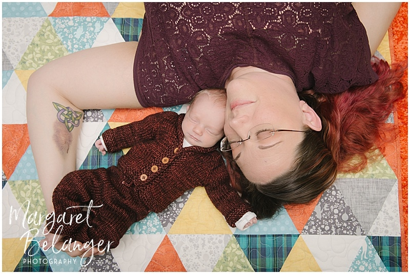 Lowell newborn session, baby in hand knit suit snuggled with mom on quilt