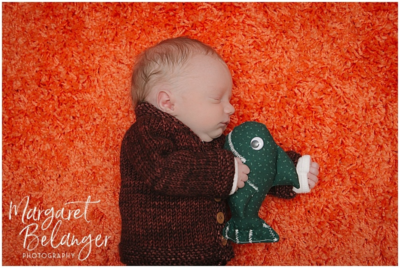 Lowell newborn session, baby in hand knit suit on orange rug