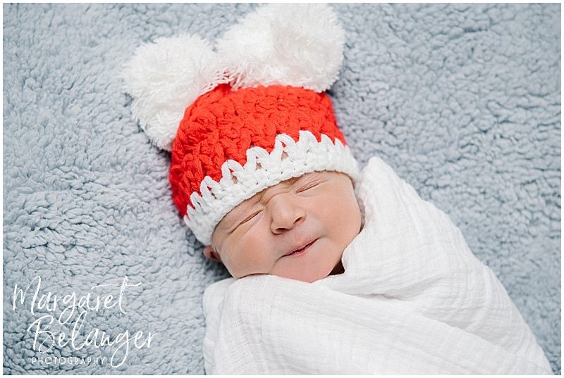 Baby in red Christmas hat at her New Hampshire newborn session