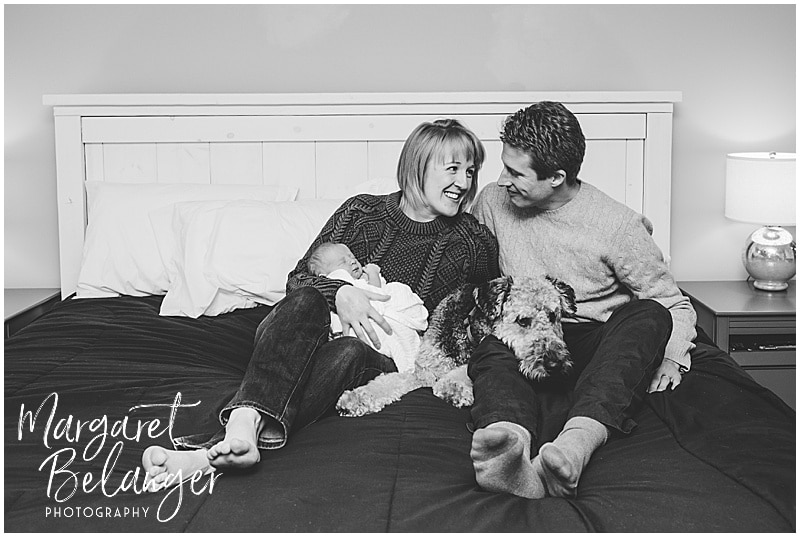 Parents on bed with newborn and dog, New Hampshire newborn session