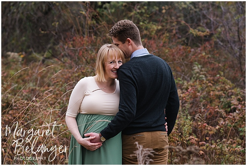 New Hampshire apple orchard autumn maternity session, couple snuggling