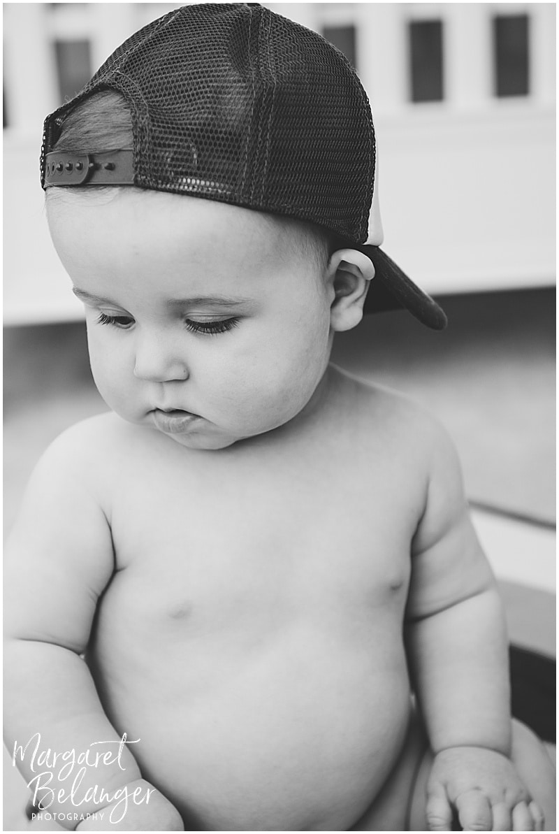 7 month old in a backwards baseball cap at his Rhode Island family session