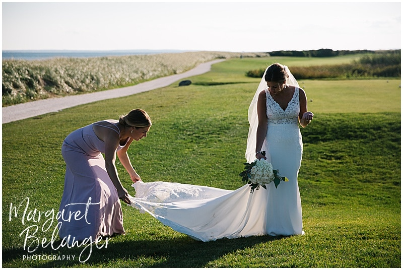New Seabury Country Club wedding, bride's sister fixing the wedding gown on the golf course