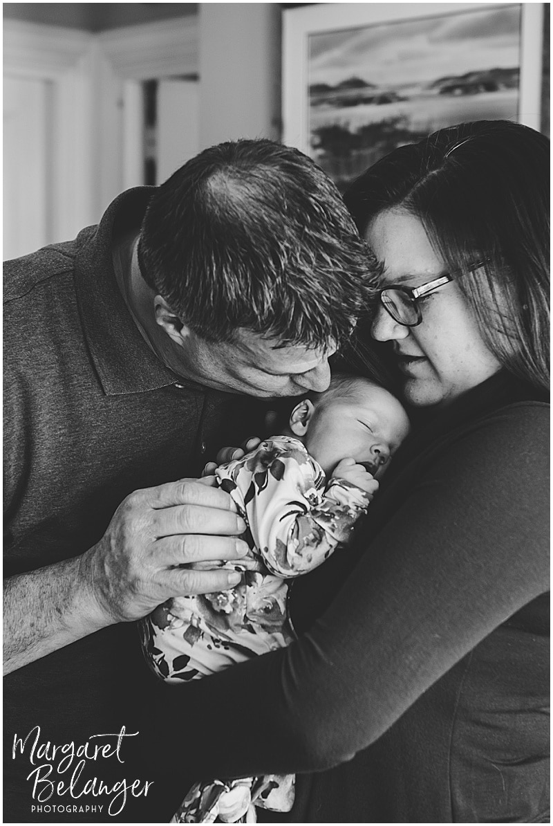South Shore newborn session, mom holding baby girl on her shoulder and dad kisses her
