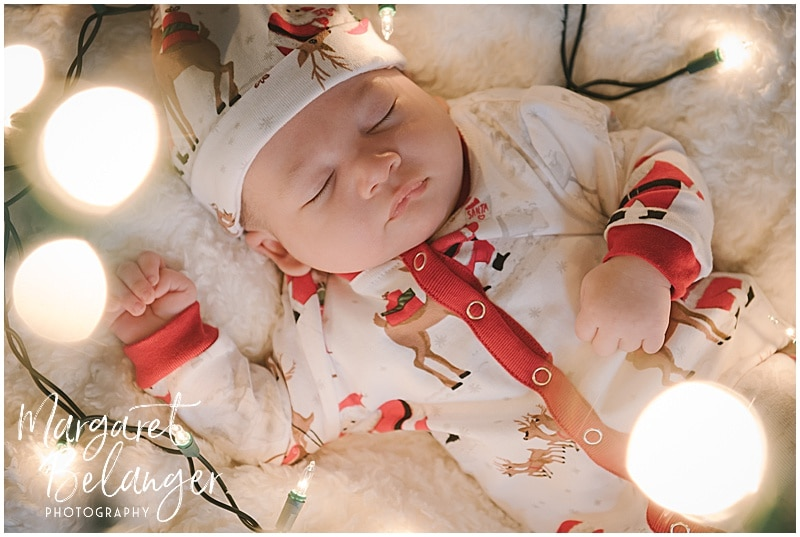 Infant in Christmas pajamas with twinkle lights around him