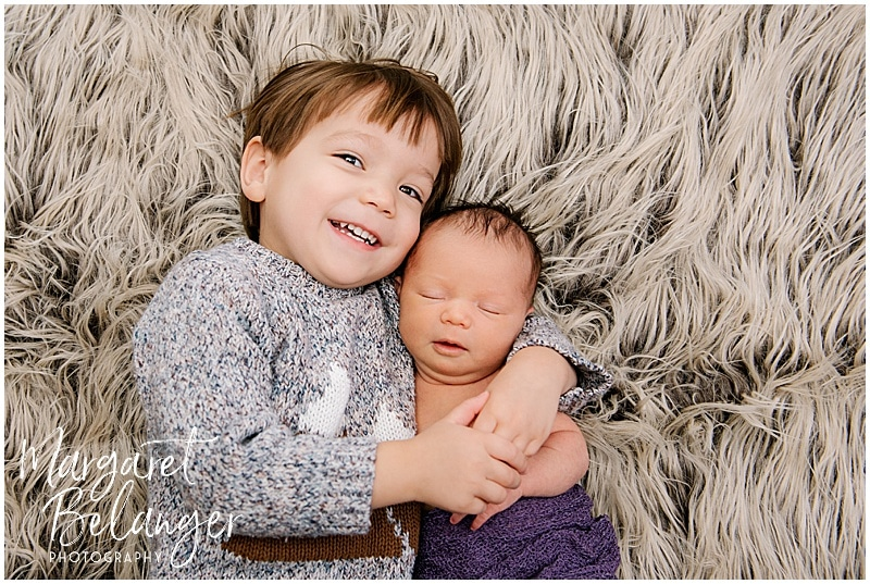 Big brother cuddling newborn sister in Medford Newborn session