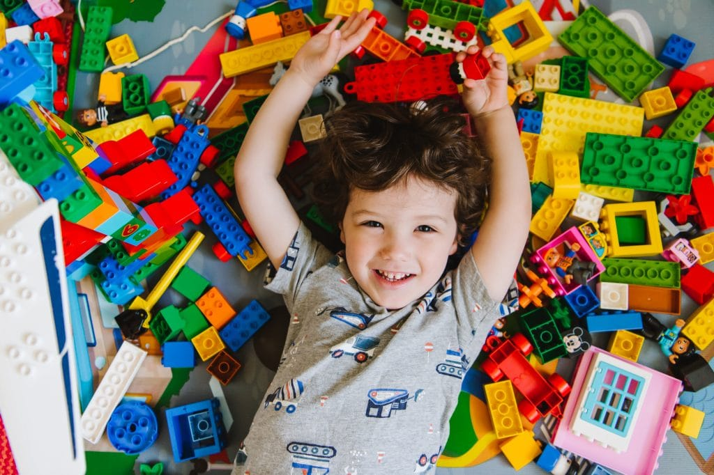 Boy lying down with colorful legos all around his head