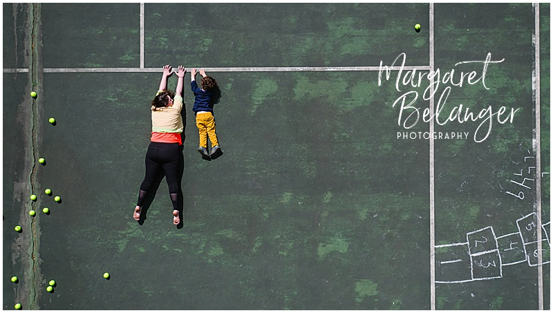 Drone portrait of a woman and little boy hanging from a line on a tennis court