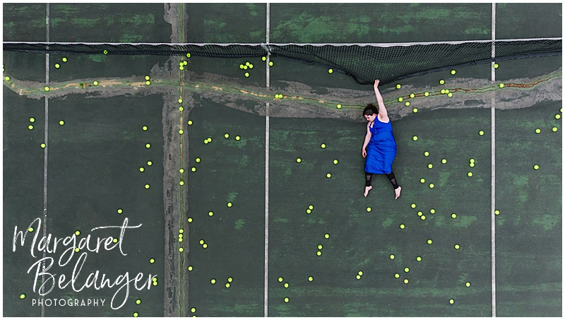 Drone portrait of a woman hanging from the net on a tennis court