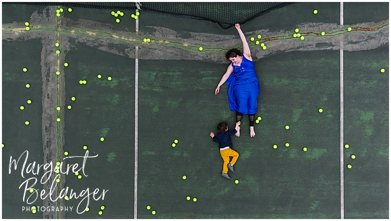 Drone portrait of a woman and a little boy hanging from the net on a tennis court