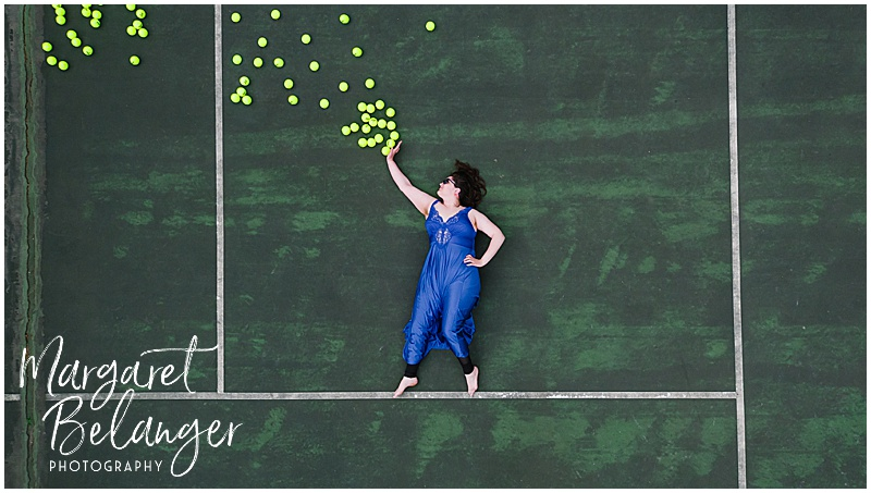 Drone portrait of a woman on a tennis court pushing balls away